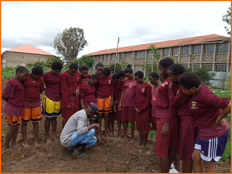 Dominic Nzavi teaching students how to plant onion seedlings