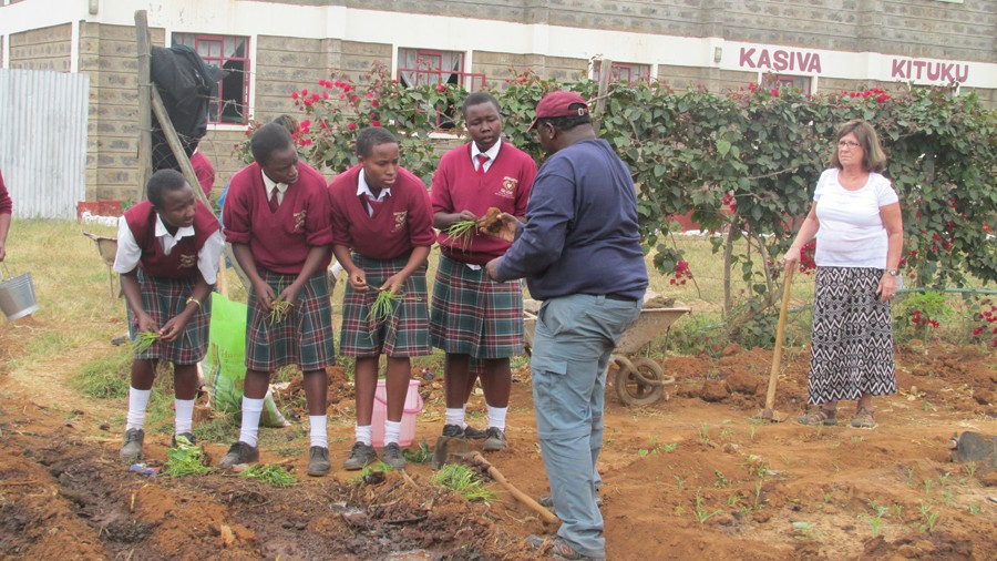 Vincent Kituku teaching Caring Hearts High School students how to plant onions